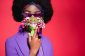 african american young woman in purple stylish outfit with flowers in inhaler isolated on red