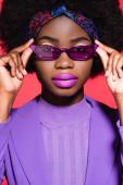 africký americký mladý žena v fialové stylové oblečení a sluneční brýle izolované na červené