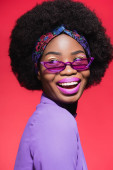 happy african american young woman in purple stylish outfit and sunglasses isolated on red
