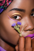 closeup of african american young woman with purple flower
