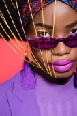 african american young woman in purple stylish outfit and sunglasses with yellow strings on face isolated on red