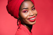 smiling african american young woman in stylish outfit and turban isolated on red