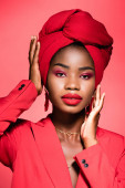african american young woman in stylish outfit and turban isolated on red