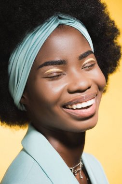 Laughing african american young woman in blue stylish outfit isolated on yellow stock vector