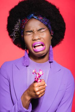 sad african american young woman in purple stylish outfit with flower crying isolated on red