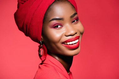 Smiling african american young woman in stylish outfit and turban isolated on red stock vector