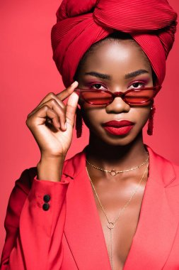 African american young woman in stylish outfit, sunglasses and turban isolated on red stock vector