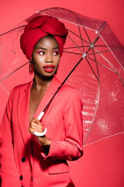 African american young woman in stylish outfit and turban holding umbrella isolated on red stock vector