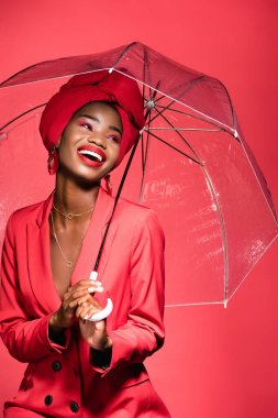 Happy african american young woman in stylish outfit and turban holding umbrella isolated on red stock vector