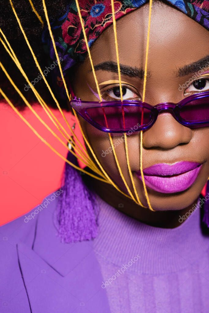 African american young woman in purple stylish outfit and sunglasses with yellow strings on face isolated on red stock vector