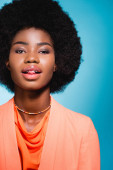 african american young woman in orange stylish outfit showing tongue isolated on blue