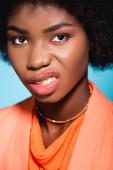 rozzlobený africký americký mladý žena v oranžový stylový outfit ukazující zuby izolované na modré