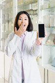 Photo excited asian pharmacist in white coat covering mouth while holding smartphone with blank screen in drugstore