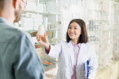 cheerful asian pharmacist in white coat holding clipboard and bottle with medication in outstretched hand near man in drugstore
