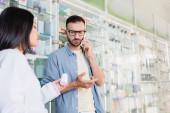 Kunde in Brille unterhält sich mit Smartphone in der Nähe eines asiatischen Apothekers mit Medikamentenflasche im verschwommenen Vordergrund