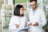 Apotheker in weißen Kitteln betrachten Flaschen mit Medikamenten in der Drogerie