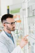 Fotografie Apotheker in weißem Kittel und Brille zeigt mit Finger in Drogerie