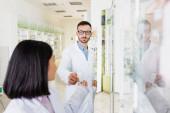 bärtiger Apotheker mit Brille und weißem Mantel gibt Flasche mit Pillen an brünetten asiatischen Kollegen auf verschwommenem Vordergrund