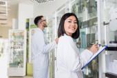 Fotografie glücklicher asiatischer Apotheker in weißem Mantel schreibt auf Klemmbrett neben Kollege auf verschwommenem Hintergrund