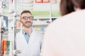 Lächelnder Apotheker in weißem Kittel und Brille, der den Kunden im verschwommenen Vordergrund anschaut