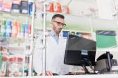 Apotheker in weißem Kittel und Brille überrascht mit Blick auf Computermonitor in Drogerie