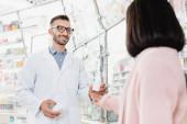 Gut gelaunter Apotheker mit Brille und weißem Kittel, der im verschwommenen Vordergrund Flaschen mit Pillen in Kundennähe hält