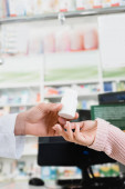 cropped view of pharmacist giving bottle with pills to customer