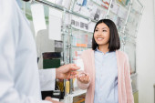 pharmacist giving bottle with pills to cheerful asian woman in drugstore