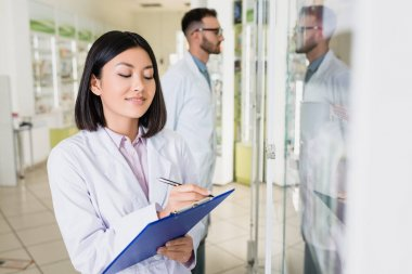 Cheerful asian pharmacist in white coat writing on clipboard near colleague on blurred background stock vector