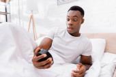 Nadšený africký Američan při pohledu na hodiny na rozmazané popředí na posteli v dopoledních hodinách