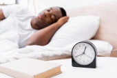 Hodiny a kniha na nočním stolku v blízkosti africké Američan muž spí na rozmazaném pozadí