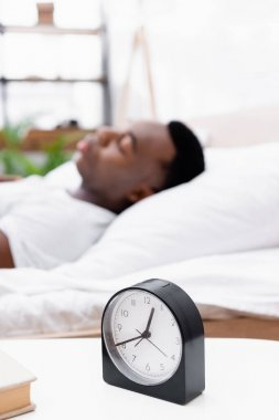Clock and book on bedside table near african american man sleeping on blurred background stock vector