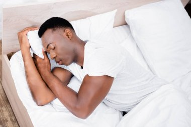 High angle view of african american man sleeping on white bedding at home stock vector