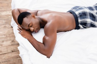 African american man in checkered pants sleeping on white bedding stock vector