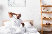Veselý afroameričan muž protáhnout na posteli v dopoledních hodinách