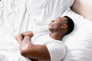 High angle view of african american man with crossed arms sleeping on bed at morning stock vector