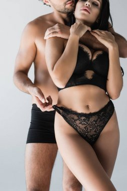 Cropped view of man in underpants touching panties of sexy girlfriend isolated on grey stock vector