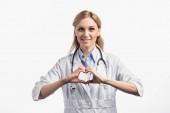 šťastný zdravotní sestra v bílém kabátě s úsměvem při zobrazení slyší znamení s rukama izolované na bílém