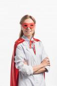 glücklich Krankenschwester in Superheldenmaske und Mantel stehend mit verschränkten Armen isoliert auf weiß