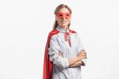 fröhliche Krankenschwester in Superheldenmaske und Mantel mit verschränkten Armen auf weißem Grund stehend
