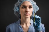 Spritze mit Impfstoff in der Hand einer Krankenschwester in Latex-Handschuh auf verschwommenem Hintergrund isoliert auf dunkelgrau