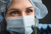 Nahaufnahme einer Krankenschwester in medizinischer Maske, die Spritze mit Impfstoff im unscharfen Vordergrund hält, isoliert auf dunkelgrau