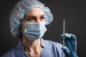 Krankenschwester in medizinischer Maske hält Spritze mit Impfstoff im unscharfen Vordergrund isoliert auf dunkelgrau