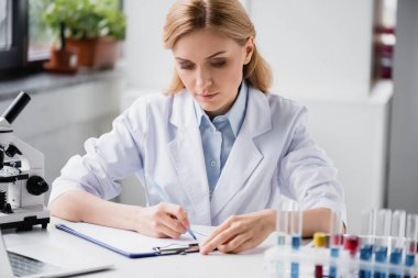 Scientist writing on clipboard near microscope and test tubes on blurred background stock vector