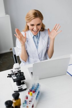 Cheerful scientist in white coat looking at laptop near microscope on desk stock vector