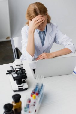 Sad scientist  in white coat covering face near laptop and microscope on desk stock vector
