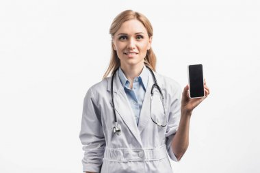 Cheerful nurse in white coat smiling while holding smartphone with blank screen isolated on white stock vector