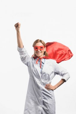 Happy nurse in superhero mask and cloak standing with raised hand isolated on white stock vector