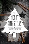 Horní pohled na perníkové sušenky poblíž borovice pokryté cukrovým práškem a veselé Vánoce a šťastný nový rok psaní