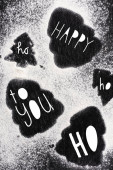 Top view of pine silhouettes covered with sugar powder with happy, ho ho ho, to you lettering